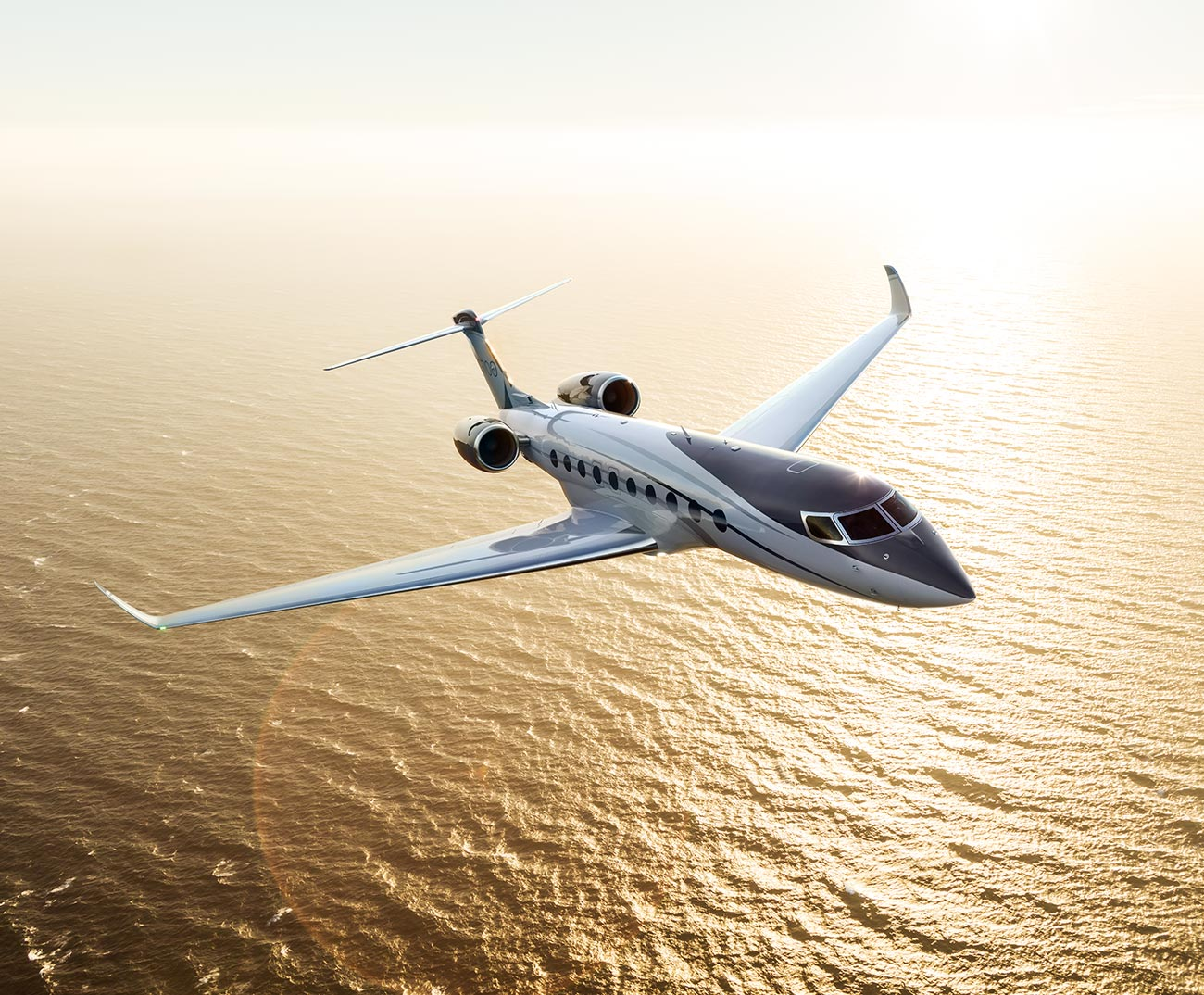 G700 flying at sunset over water